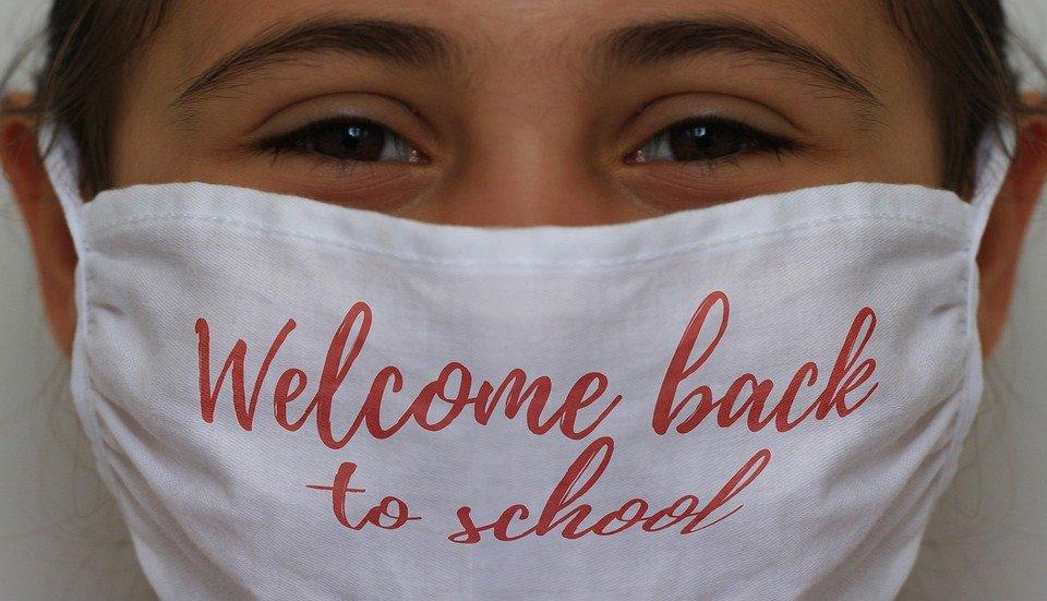 Girl wearing welcome back to school face mask amidst coronavirus