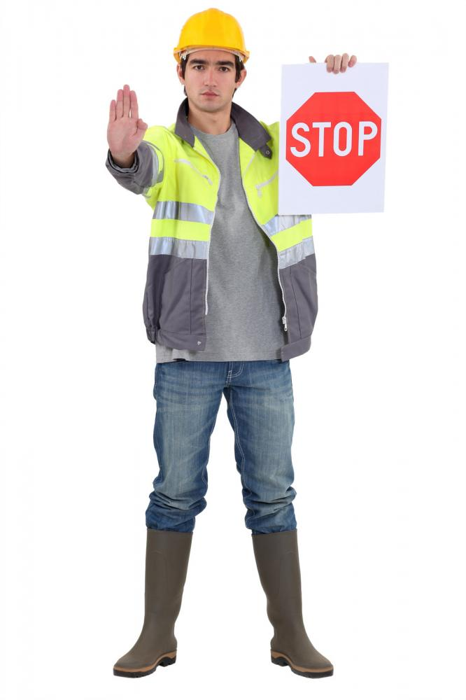Traffic controller gesturing to halt with a stop sign