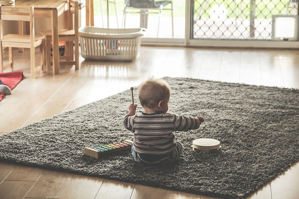 A baby playing with a tambourine and a xylophone