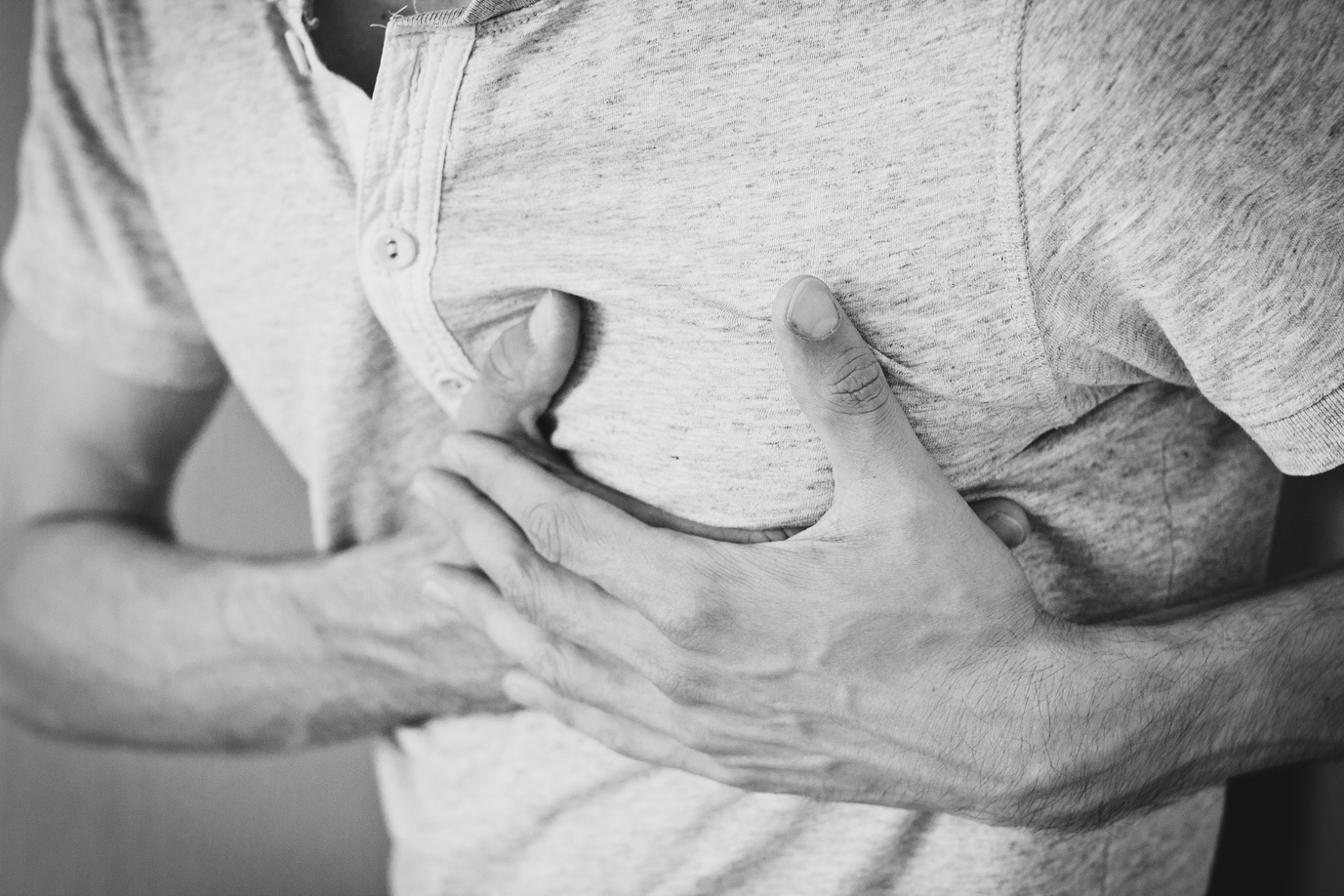 A person clutching their chest due to severe angina pain